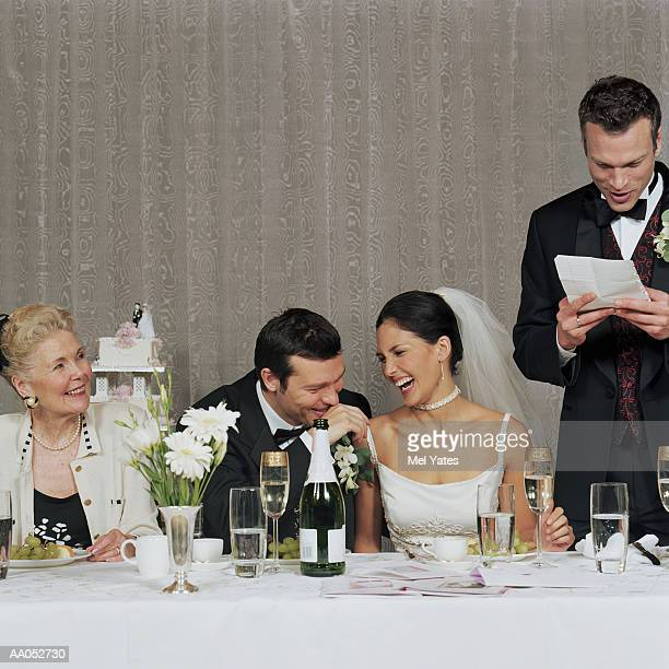 Bride and groom laughing at best man's toast