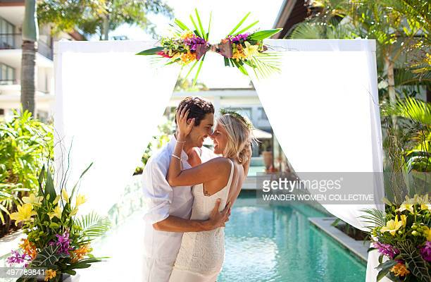 Bride and groom laughing  kissing tropical resort