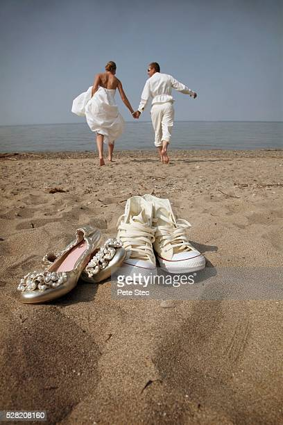 52316967e0a208 A Bride And Groom Leaving Their Shoes And Walking Barefoot On A Beach