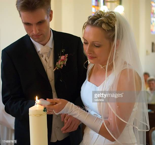 bride and groom lighting candle