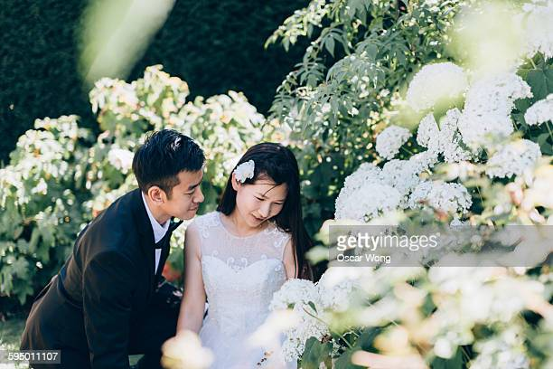 Bride and groom looking at flowers in garden
