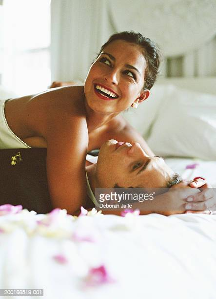 Bride and groom lying on bed, woman looking up