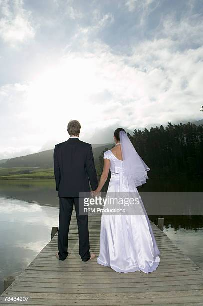 Bride and groom on jetty, looking at lake, rear view