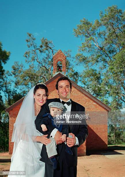 Bride and groom outside church, groom holding boy (9-12 months)