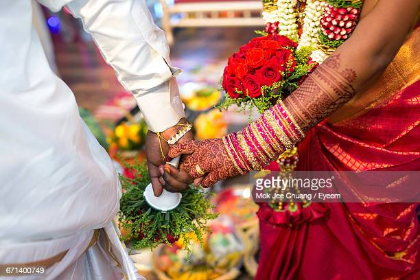 bride and groom performing traditional rituals in wedding - sposi foto e immagini stock