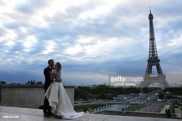 A bride and groom pose early on September 15 2015 for a souvenir photograph at the Trocadero Plaza with the Eiffel Tower as a back drop in the French...