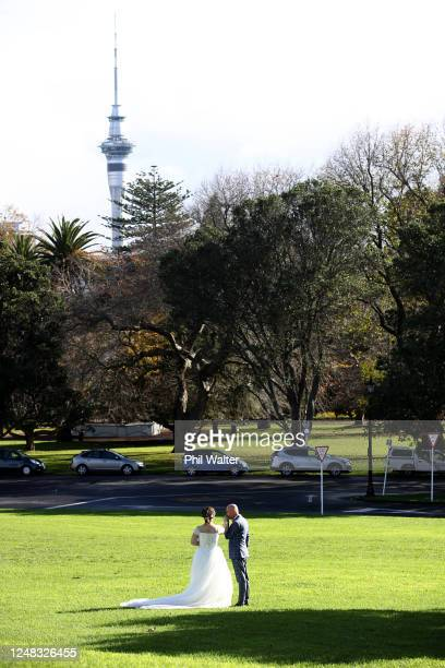 Bride and groom pose for a photo in the Auckland domain on June 09, 2020 in Auckland, New Zealand. COVID-19 restrictions lifted at midnight as New...