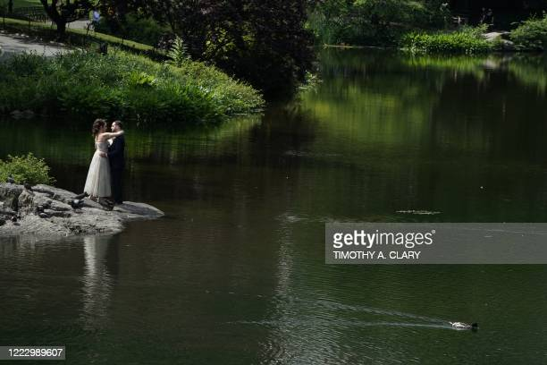 Bride and groom pose for pictures for their photographer at the pond in Central Park June 26, 2020. - The governors of New York, New Jersey and...
