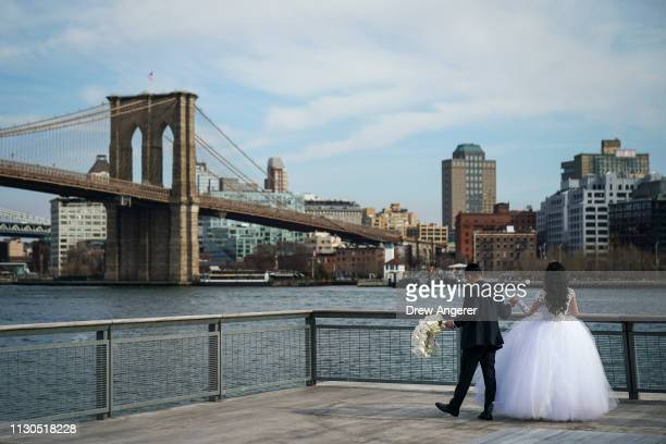 A bride and groom pose for wedding photos along the East River at South Street Seaport March 14 2019 in New York City Mayor Bill de Blasio has...