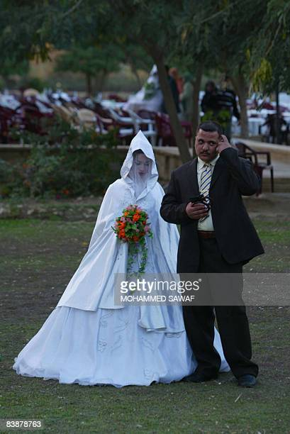 A bride and groom pose on the lawn following a mass wedding ceremony in the grounds of ancient Babylon some 100 kms south of Baghdad on December 01...