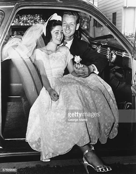 Bride and Groom posing in car, (B&W), portrait
