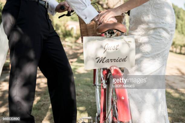 a bride and groom push a bicycle with a just married sign on the back - just married stock pictures, royalty-free photos & images