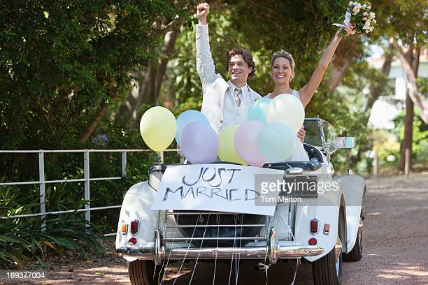 Bride and groom riding in convertible