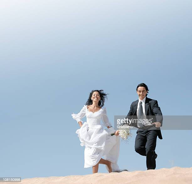 Bride and groom running in the dunes