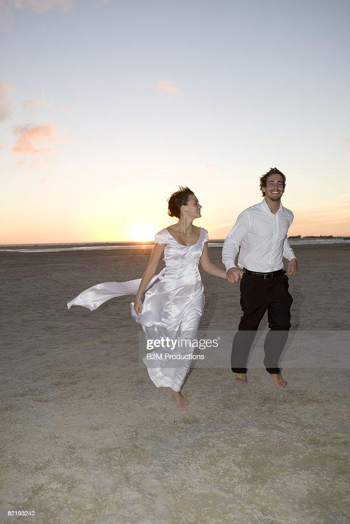 Bride and groom running on beach holding ha : Stock Photo