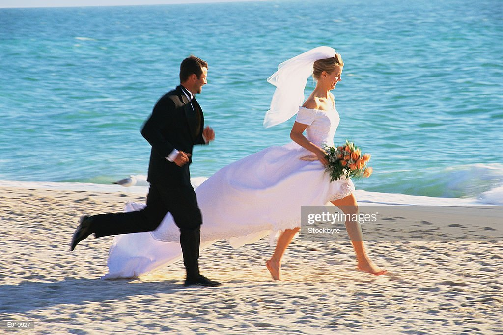 Magnificent Bride And Groom Running On Beach Stock Photo Getty Images Download Free Architecture Designs Scobabritishbridgeorg