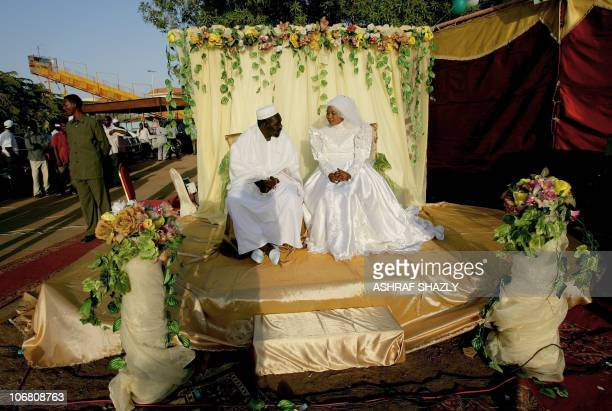 A bride and groom sit together for a photograph during a mass wedding of some 1000 couples in what has been dubbed the 'Marriage of Unity' on...