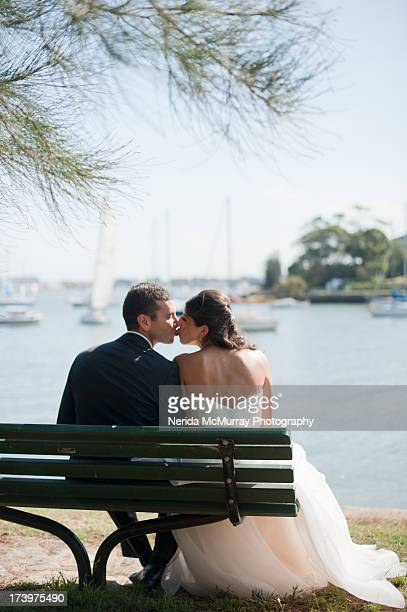 bride and groom sitting and kissing - backs - lebanese ethnicity stock photos and pictures