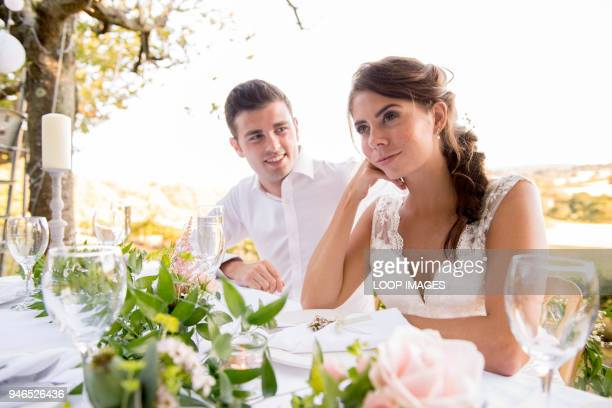 a bride and groom sitting at the top table at an outside wedding - bride stock photos and pictures