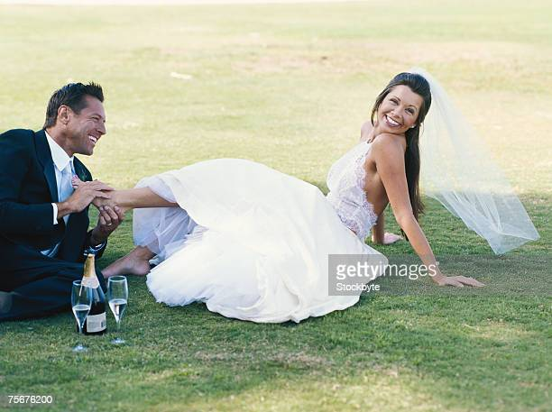 Bride and groom sitting on lawn, smiling