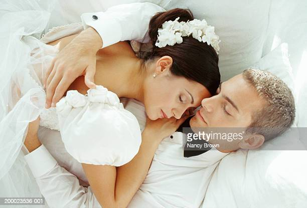 bride and groom sleeping in embrace, elevated view - romantic young couple sleeping in bed stock photos and pictures