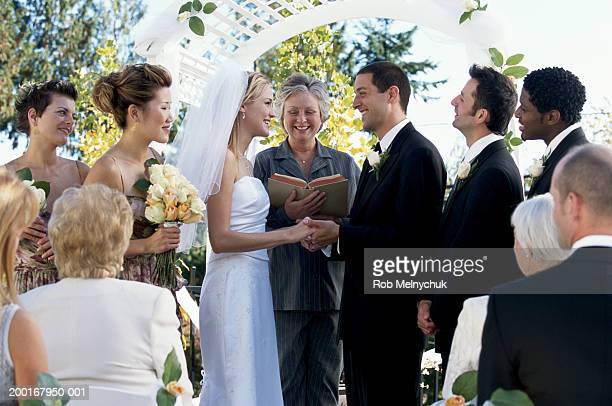 bride and groom smiling at each other while minister performs ceremony - wedding vows stock pictures, royalty-free photos & images