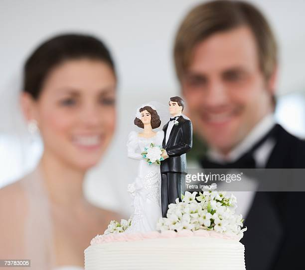 Bride and groom smiling at wedding cake