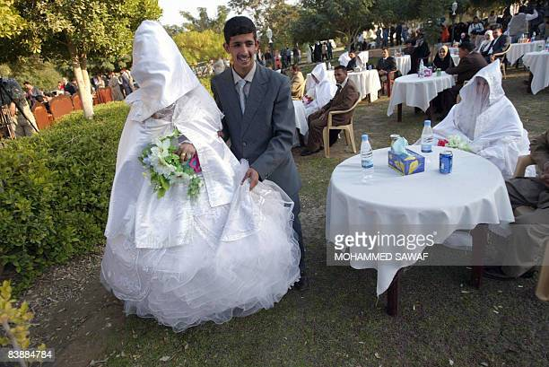 A bride and groom stand together during a mass wedding ceremony in the grounds of ancient Babylon some 100 kms south of Baghdad on December 01 2008...