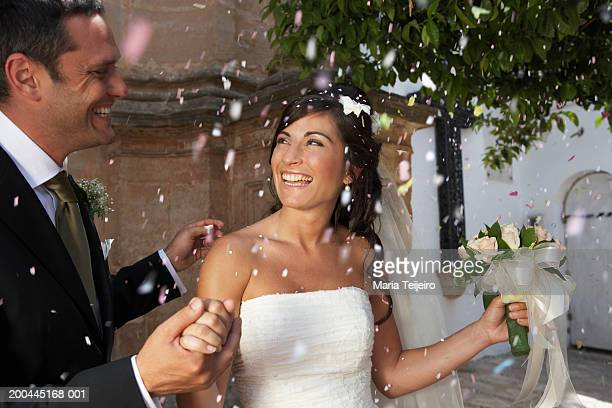 bride and groom standing amongst falling confetti, outdoors - church wedding decorations stock pictures, royalty-free photos & images