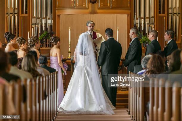 bride and groom standing at altar during wedding ceremony - kirche stock-fotos und bilder