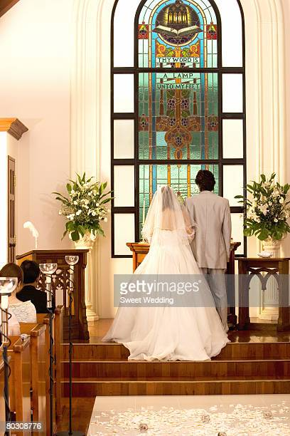 Bride and groom standing in church, rear view