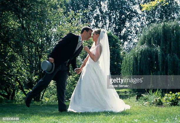 bride and groom standing in garden - tail coat stock pictures, royalty-free photos & images