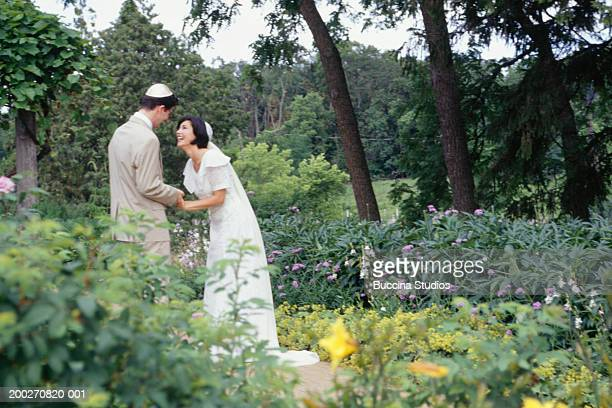 Bride and groom standing in park, side view