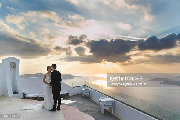 Bride And Groom Standing In Wedding Place At Santorini During Sunset
