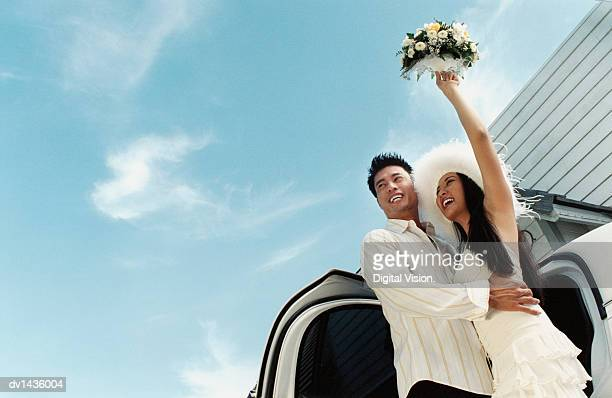 Bride and Groom Standing Next to a Car and Bride Waving With her Bouquet