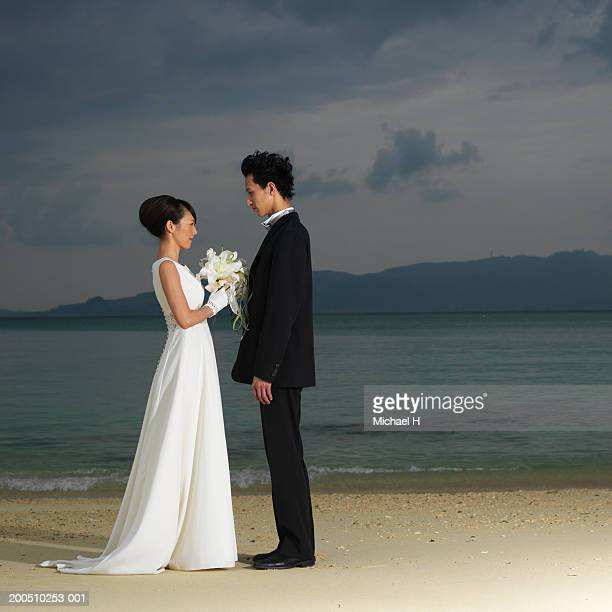 Bride and groom standing on beach, side view, dusk
