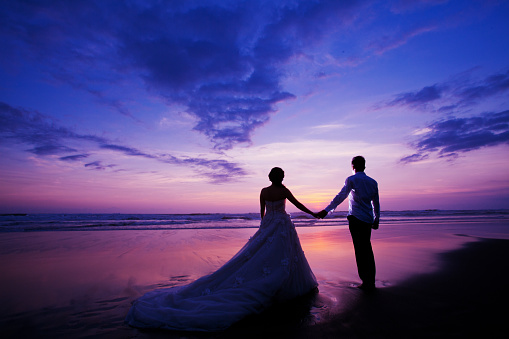 Bride And Groom Standing On Shore During Sunset - gettyimageskorea