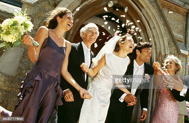 bride and groom standing outside a church with their parents and guests