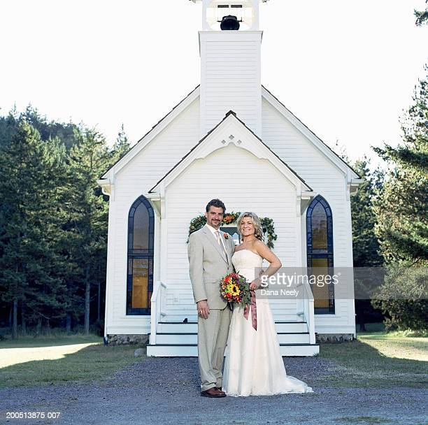 Bride and groom standing outside chapel, portrait