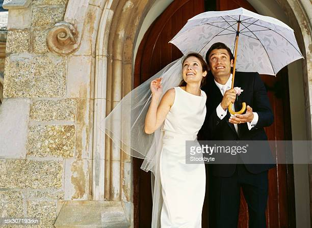 bride and groom standing under an umbrella