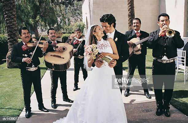 Bride and Groom Standing With a Mariachi Band in a Church Garden