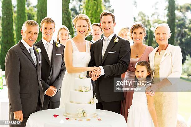Bride and Groom Standing With Guests While Cutting Wedding Cake