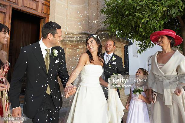 bride and groom surrounded by falling confetti, holding hands, smiling - church wedding decorations stock pictures, royalty-free photos & images