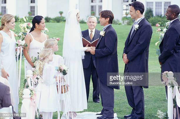 Bride and groom taking vows at outdoor wedding ceremony, side view