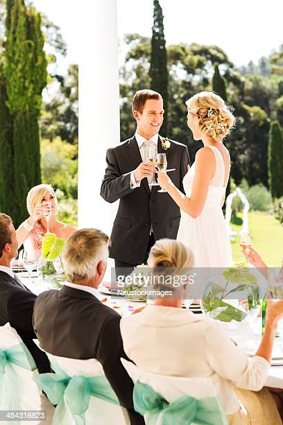 Bride And Groom Toasting Champagne Flutes During Reception