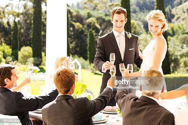 Bride and Groom Toasting Champagne Flutes With Guests During Reception
