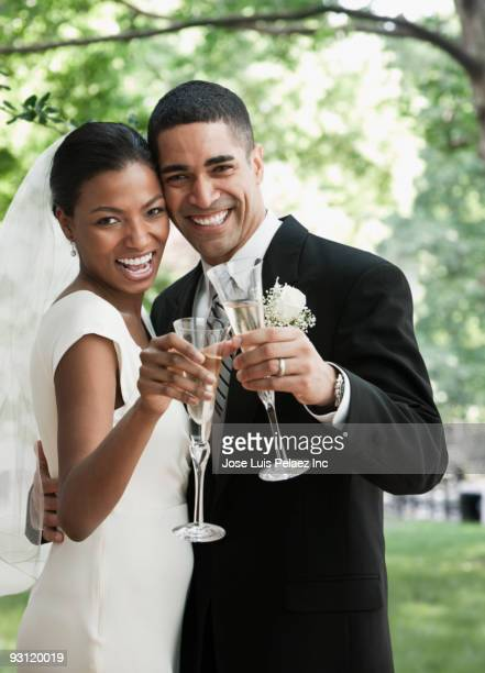 Bride and groom toasting champagne glasses