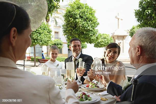 Bride and groom toasting drinks with friends and flower girl (7-9)