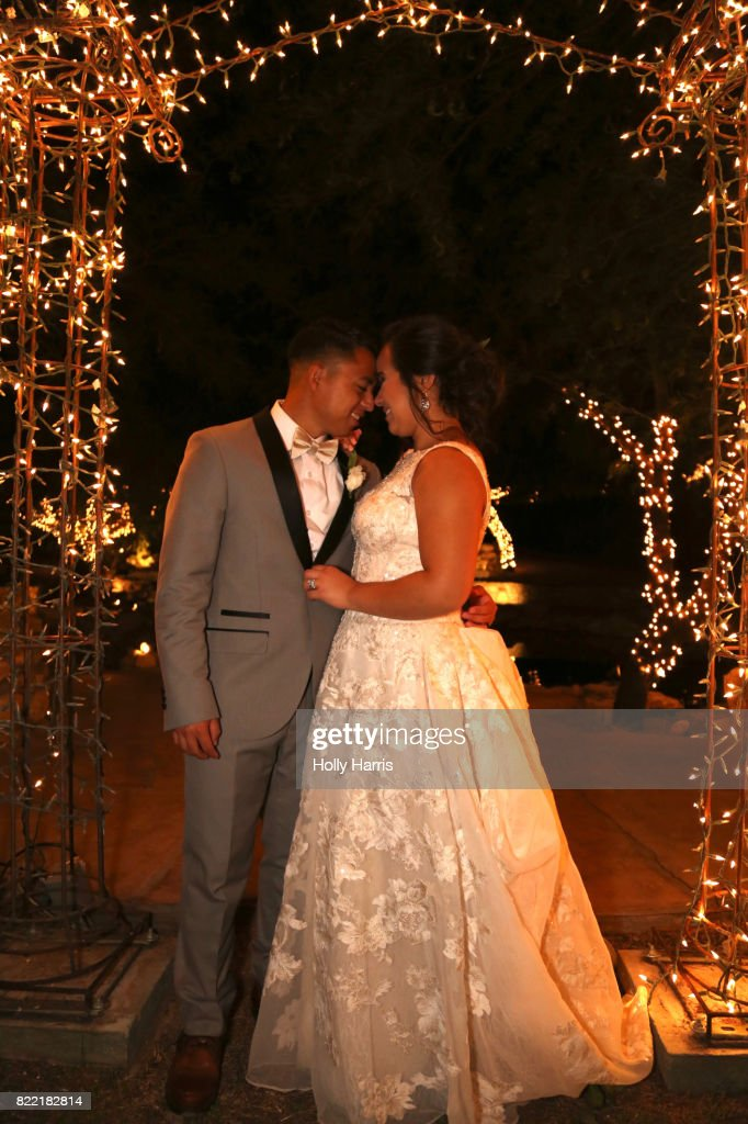 Bride and groom touching noses under illuminated arch at night : Stock Photo