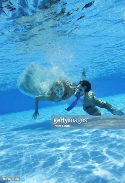 Bride and groom underwater in swimming pool